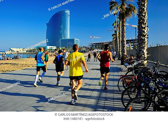 People running and Hotel W by Ricardo Bofill in background, Barceloneta, Barcelona, Catalonia, Spain