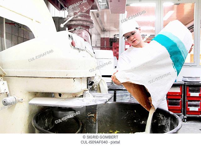 Baker pouring flour into mixer