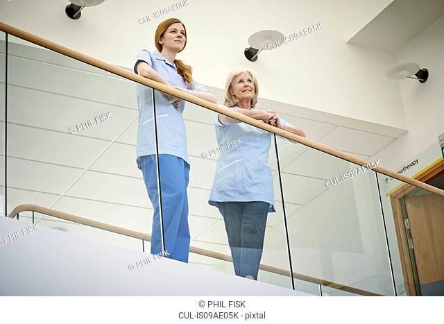 Two female nurses waiting on hospital atrium balcony