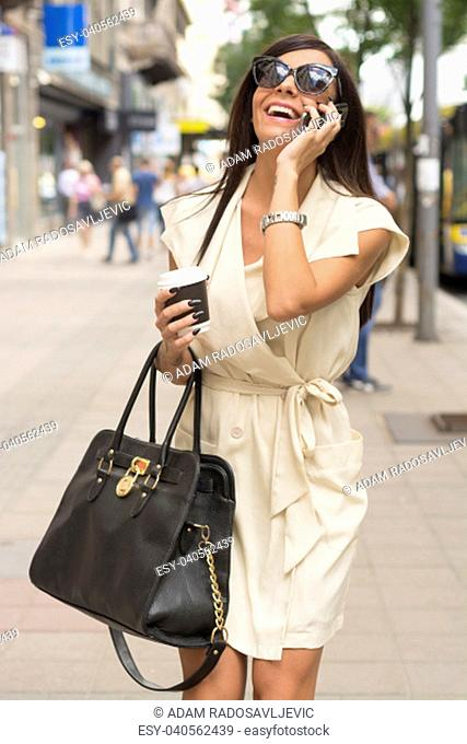 Fashionable young brunette wearing short white dress and sunglasses laughs into phone on city street near bus