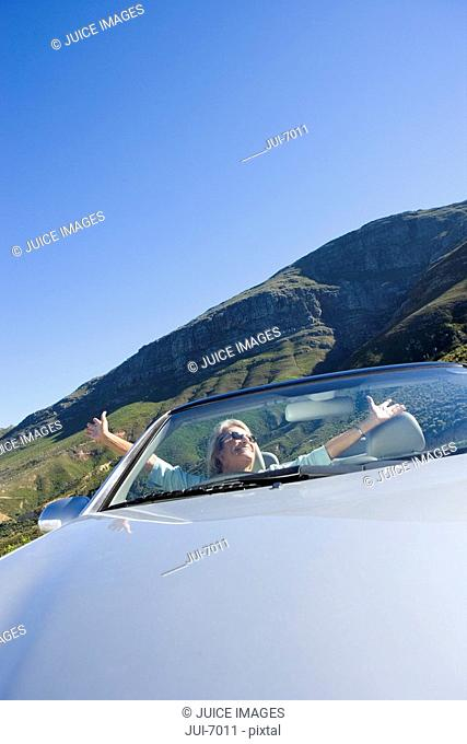 South Africa, Western Cape, senior woman sitting in silver convertible car on mountain road, arms out smiling, front view tilt