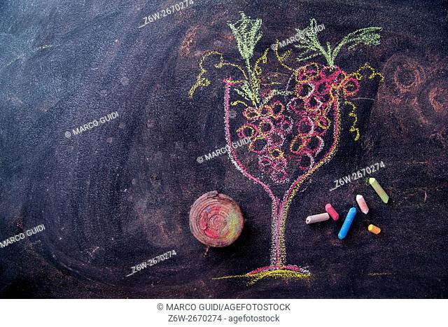 Graphical representation of a glass filled with red grapes, drawn with chalk on blackboard