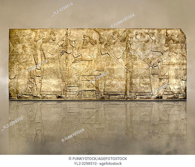 Assyrian relief sculpture panel of King Ashurnaspiral II enthroned between two attendants. The group is flanked by winged protective spirits