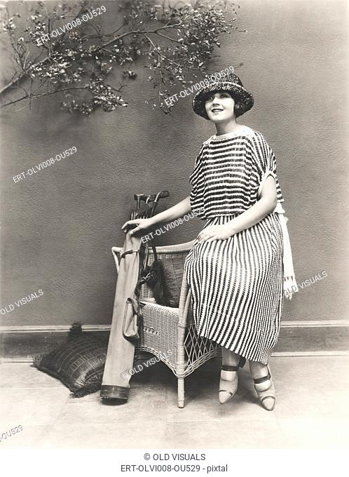 Woman in striped dress with golf clubs