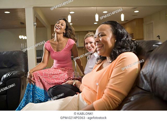 Three happy multi-ethnic women sitting in modern living room