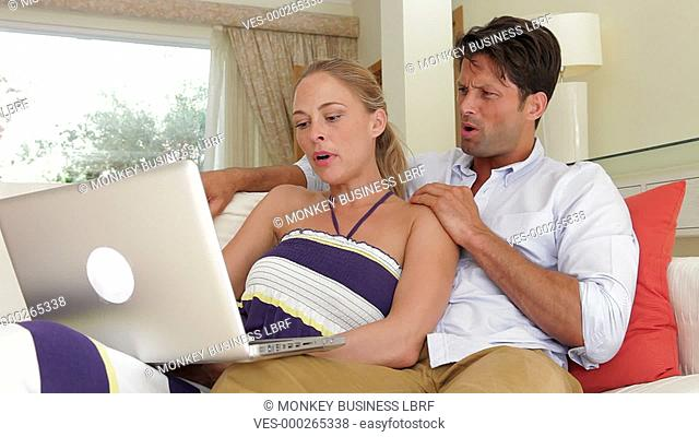 Couple sitting on sofa together as woman holds and operates laptop.Shot on Canon 5D Mk2 at at a frame rate of 30 fps