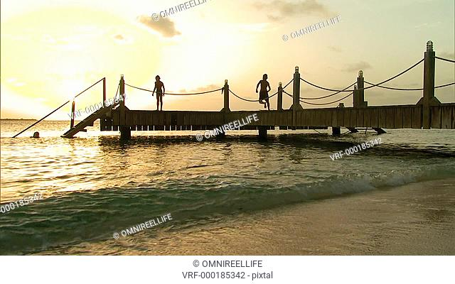 Two young boys diving into sea from wooden jetty whilst young female climbs steps to jetty in silhouette