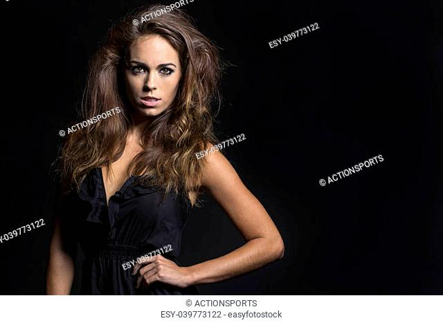 A high fashion brunette model posing in a studio environment