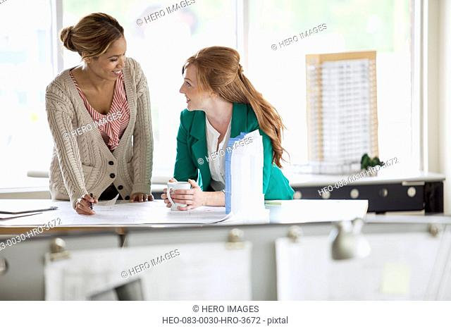 female architects discussing blueprints together