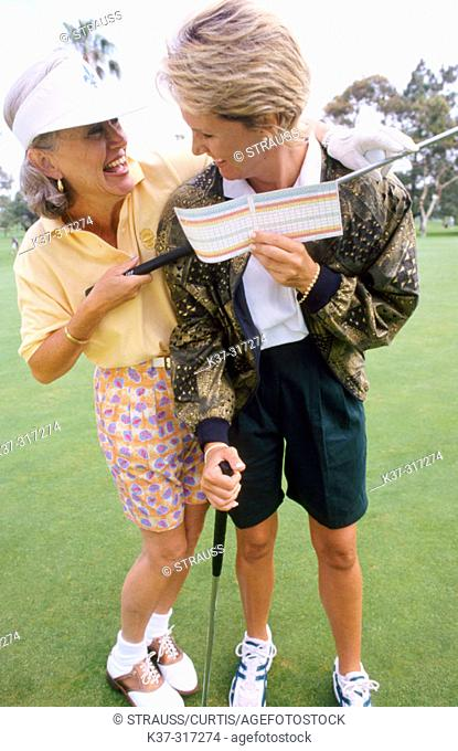 Golfing women showing their score cards