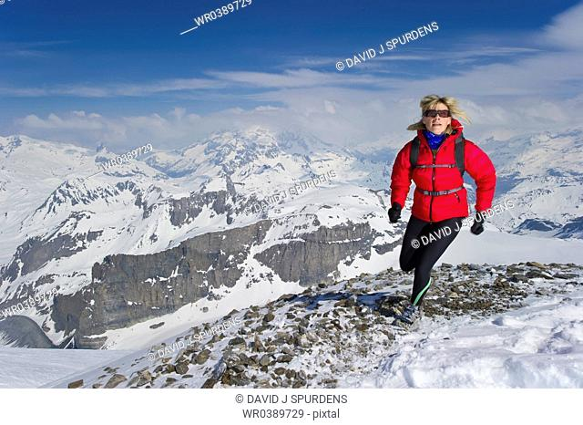 Woman jogging over high snowy peaks