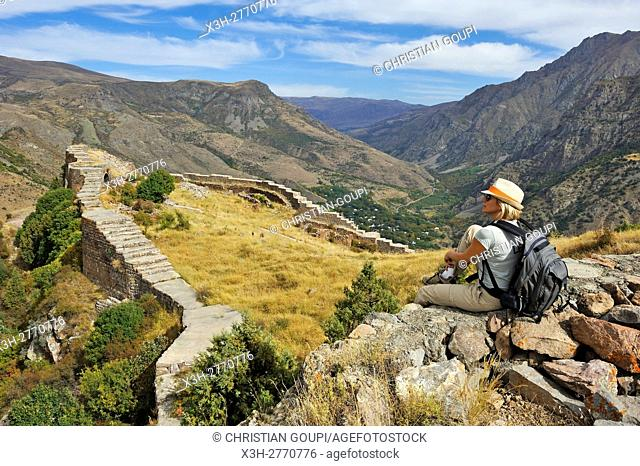 young woman sitting on a defensive wall of Smbataberd Fortress, located upon the crest of a hill between the villages of Artabuynk and Yeghegis
