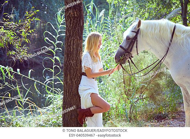 Blond girl feed grass to her white horse in a magic light forest near river