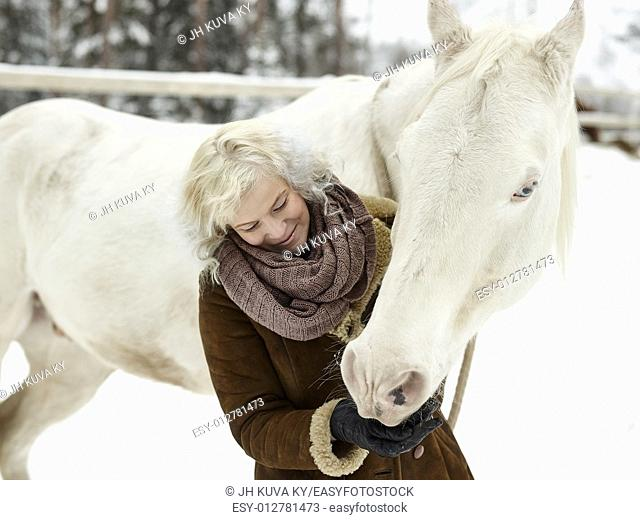 Attractive blond woman feeds a white horse, overcast winter day. South Finland in February