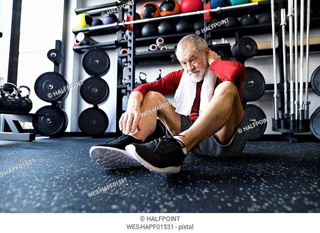 Exhausted senior man sitting on the floor after working out in gym