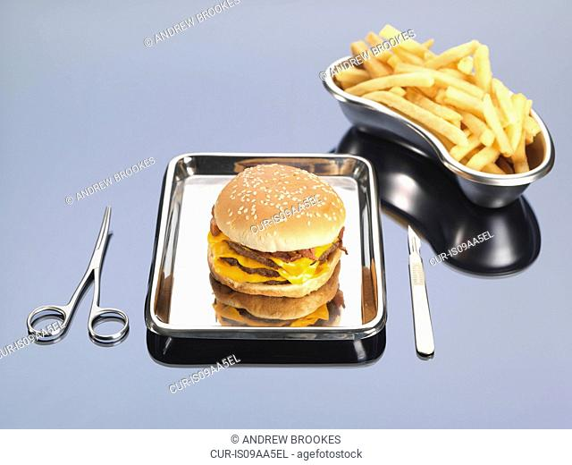 Burger and fries sitting in surgical trays illustrating unhealthy diet