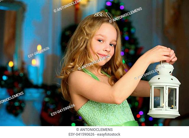 Beautiful charming pretty blond child-girl in a festive green dress with a magic lantern on the background of a New Year tree
