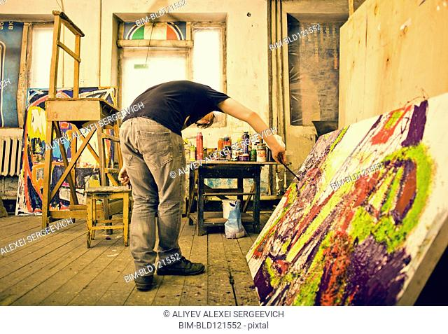 Caucasian artist painting in studio