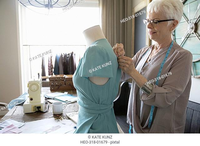 Senior woman seamstress pinning dress on dressmakers model
