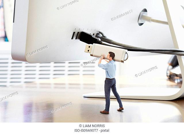 Businessman holding large USB stick next to oversized computer monitor