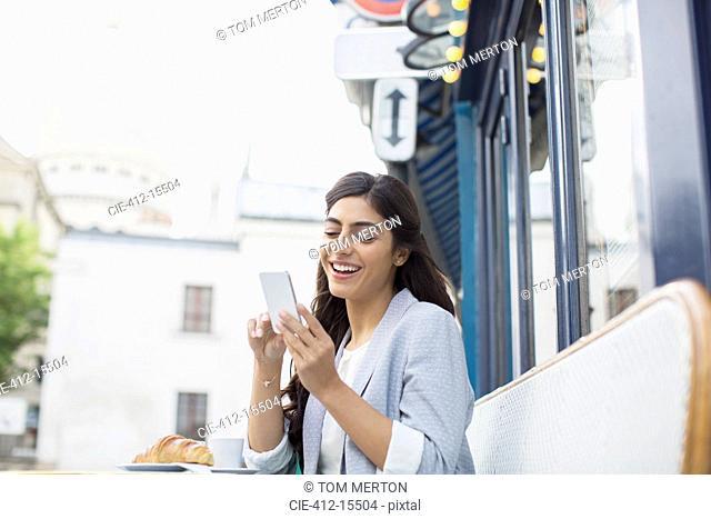 Woman using cell phone at sidewalk cafe near Sacre Coeur Basilica, Paris, France