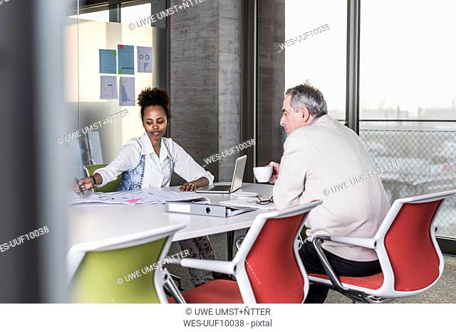 Businessman and young woman talking in conference room