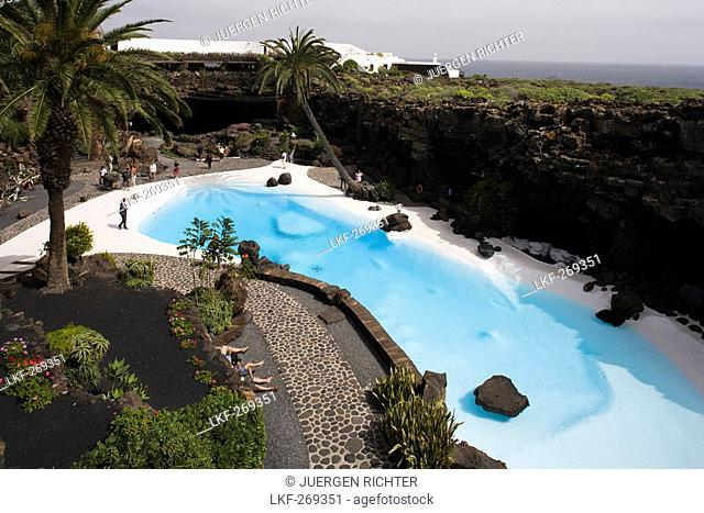 Swimming pool with palm trees near a volcanic cave, Jameos del Agua, hollow lava tunnel, architect Cesar Manrique, UNESCO Biosphere Reserve, Lanzarote