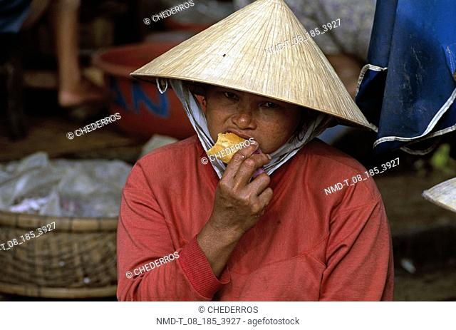 Close-up of a mid adult man eating bread, Vietnam