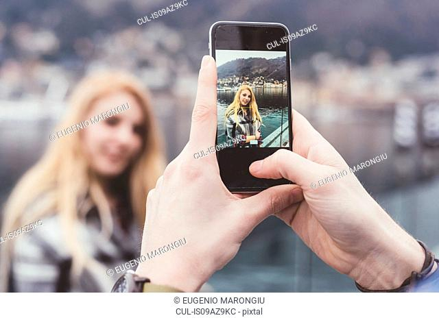 Man's hands taking smartphone photograph of girlfriend on waterfront, Lake Como, Italy