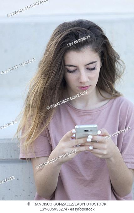 Teenage girl sitting on a ladder with her mobile looking. Shot with natural light