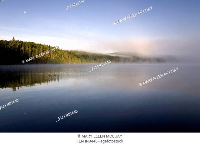 Morning mist with rising moon over Smoke Lake, Algonquin Park, Ontario