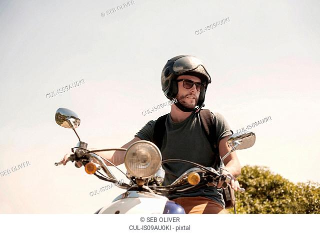 Portrait of mid adult man sitting on moped