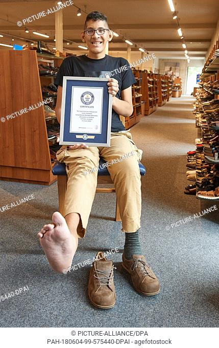 04 June 2018, Vreden, Germany: Jeison Rodriguez, the man with the world's biggest feet shows his new shoes and Certificate at the Wessels shoe house