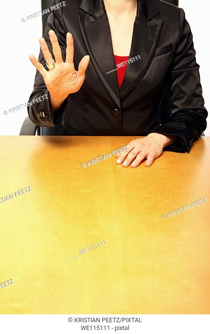View of a business-woman sitting at a desk and counting with her fingers