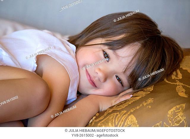 Three year old girl resting on the bed