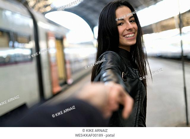 Happy young woman holding hand at train station