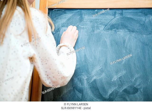 Girl writing on blank blackboard