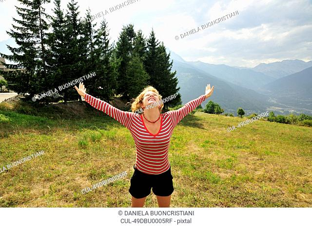 Woman jumping for joy on hillside