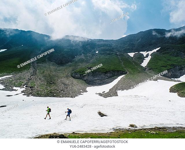 Hikers on snowfield, Val Formazza, Italy