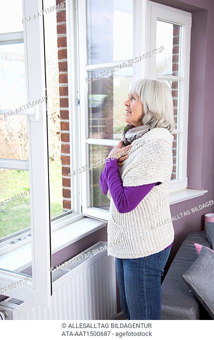 Elderly lady breathe deeply at the open window