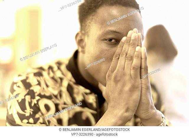 man, folded hands covering face, portrait, praying, hoping, indoors