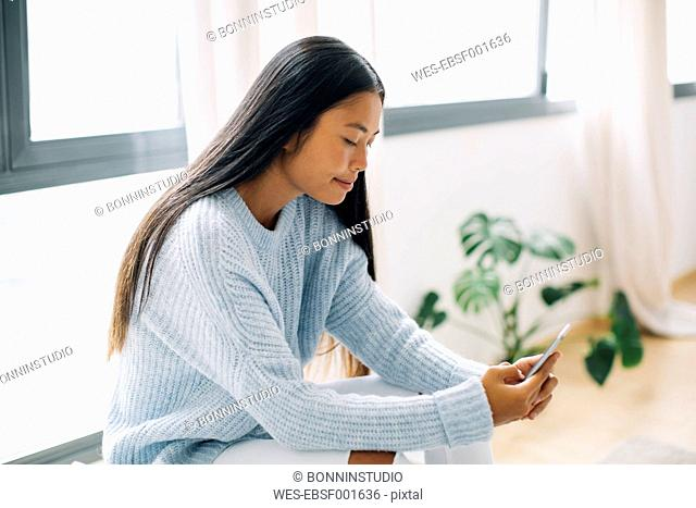 Young woman sitting at home looking at smartphone