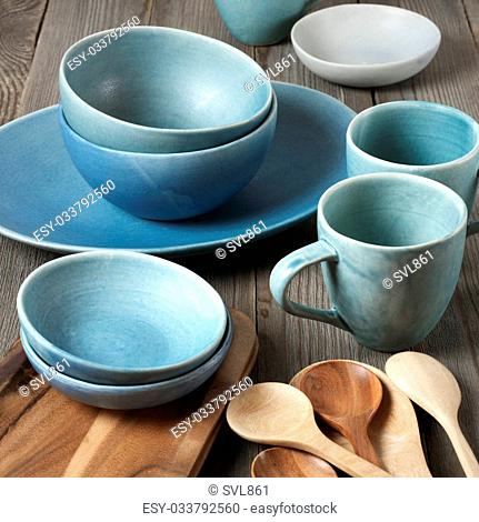 Rustic handmade blue ceramic dishware, wood tray and spoons on wooden table