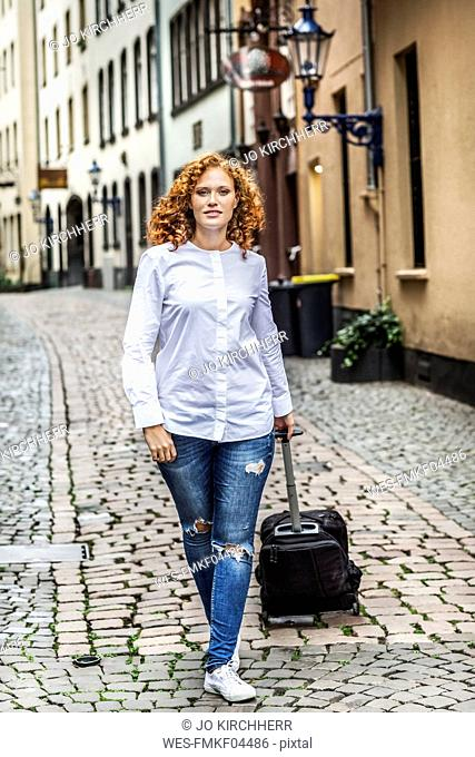 Germany, Cologne, young woman with suitcase in the old town