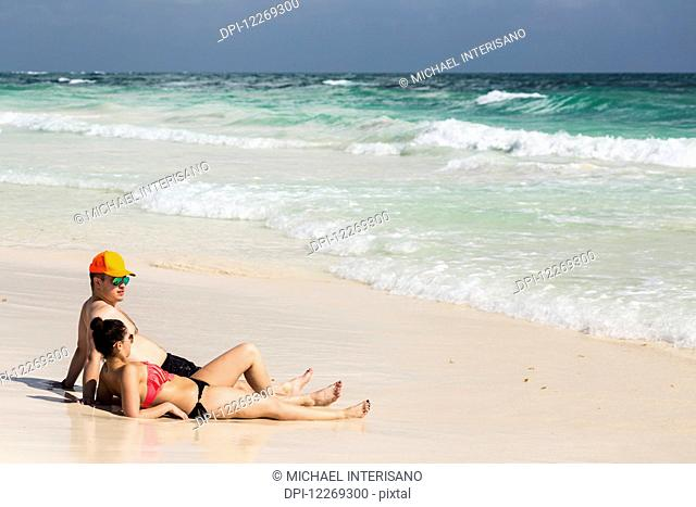 Couple laying and sitting on sandy beach with waves coming in and blue sky; Tulum, Quintana Roo, Mexico