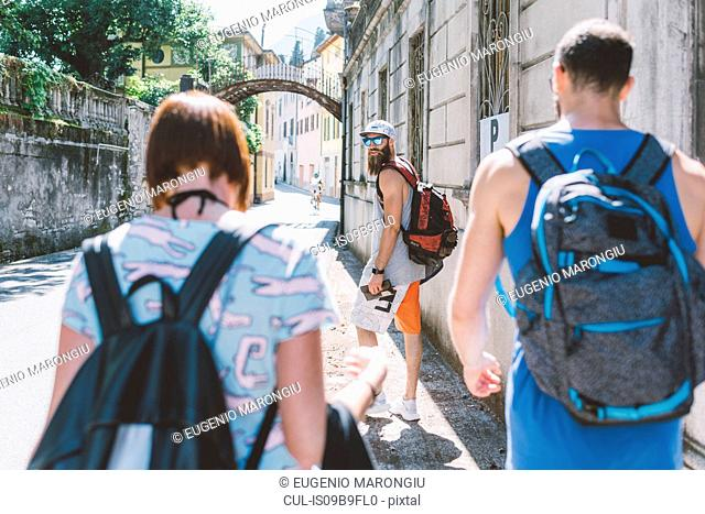 Three young hipster friends strolling along street, Como, Lombardy, Italy