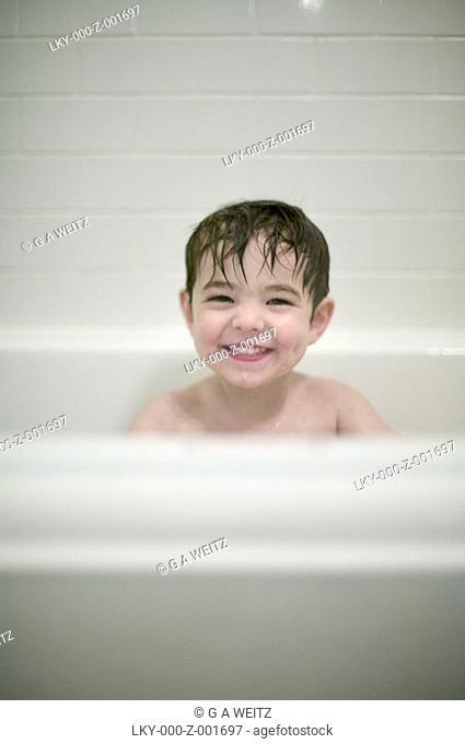 Young boy in bathtub, smiling