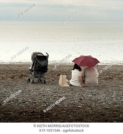 A young couple sitting under an umbrella on a deserted beach on a typically british wet summer afternoon with a child's buggy next to them  Wales UK
