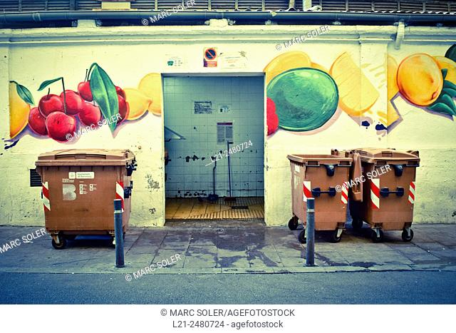 Containers in front of a wall with a painted mural of fruits. Abaceria Central market, Gracia quarter, Barcelona, Catalonia, Spain