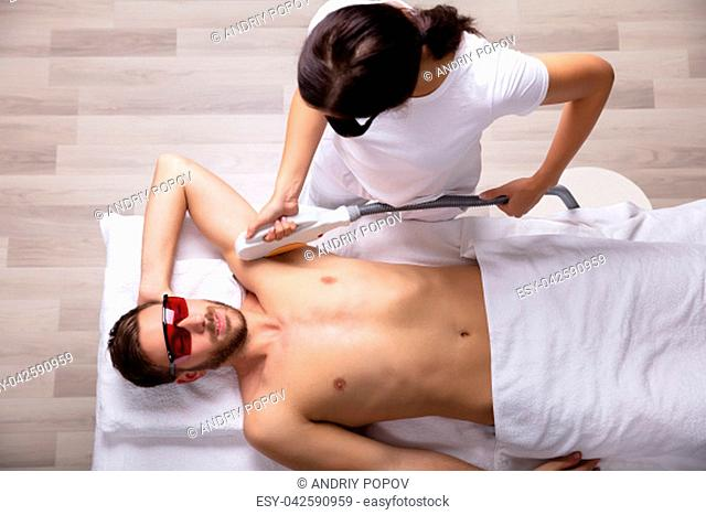 Close-up Of Smiling Young Man Having Underarm Laser Hair Removal Treatment In Spa